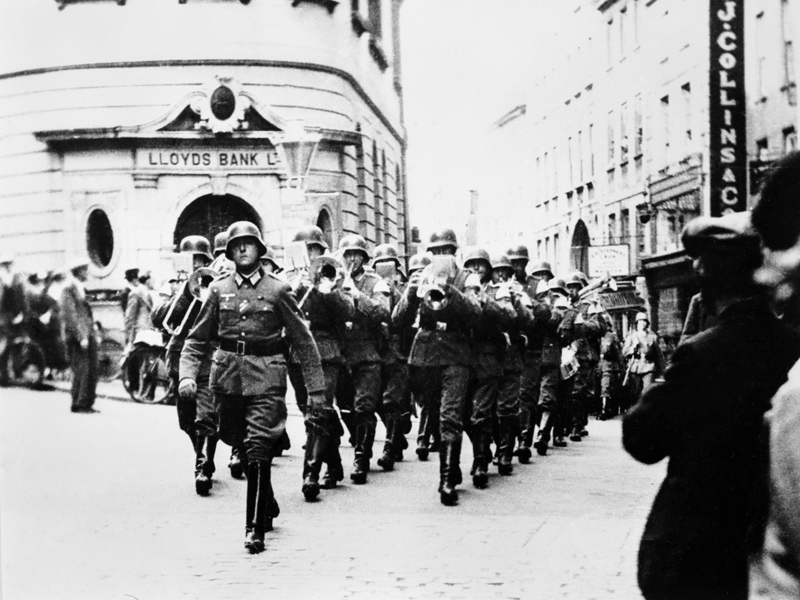 German military band marching past Lloyds Bank on The Pollet, St Peter Port. © IWM